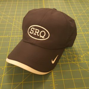 Black Nike Dri-FIT Swoosh Perforated Cap with white embroidered custom SRQ text with oval design on center.